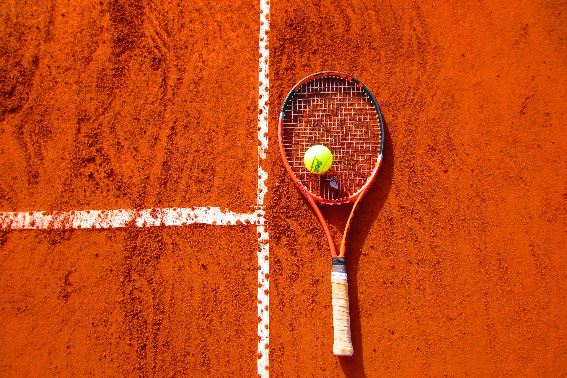 A tennis racket and ball on a clay court.