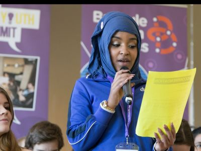 Young women reading recommendation from youth summit.