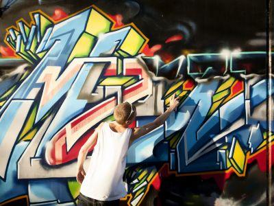 Young man doing a street art Mural.