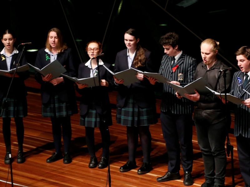 Seven high school students singing on a stage