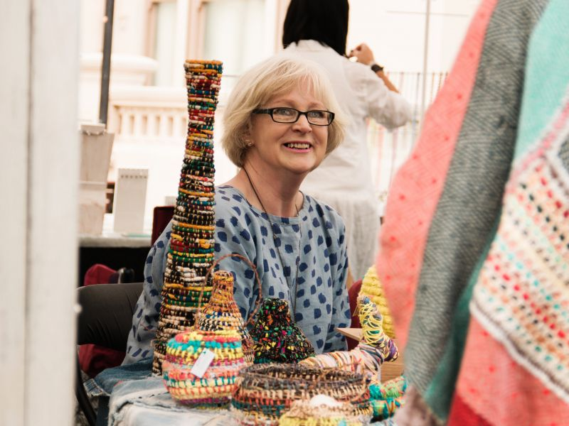 A woman sitting smiling at a table full of wool sculptures
