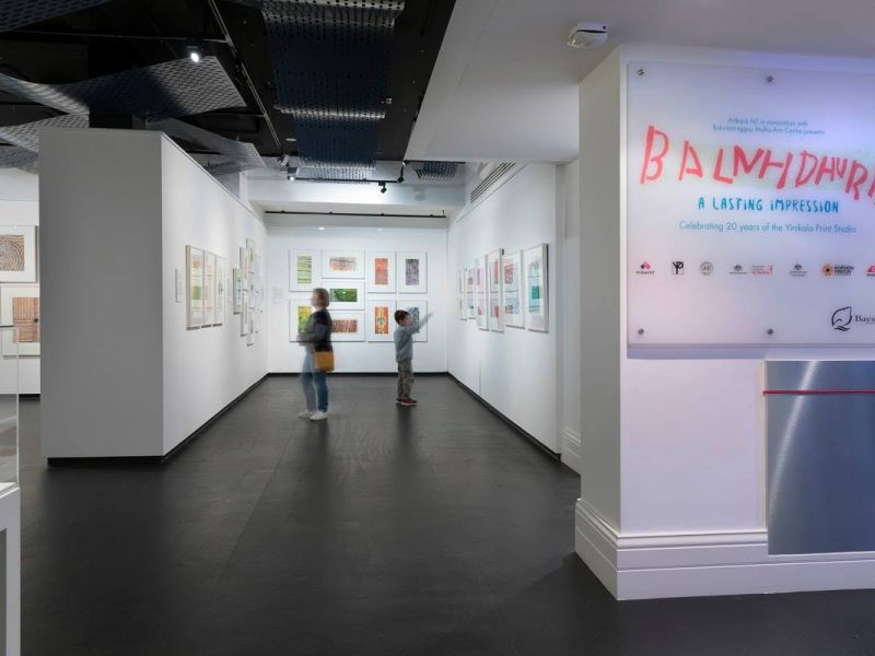 A woman and a young boy looking at colourful abstract prints in a gallery