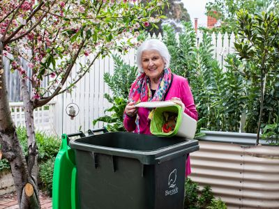Woman emptying food waste caddy into food and green waste bin