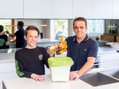 Two people putting food waste in caddy in kitchen