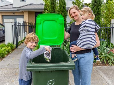 Family of people putting food waste in food and green waste bin