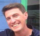Photo of a man's face smiling.