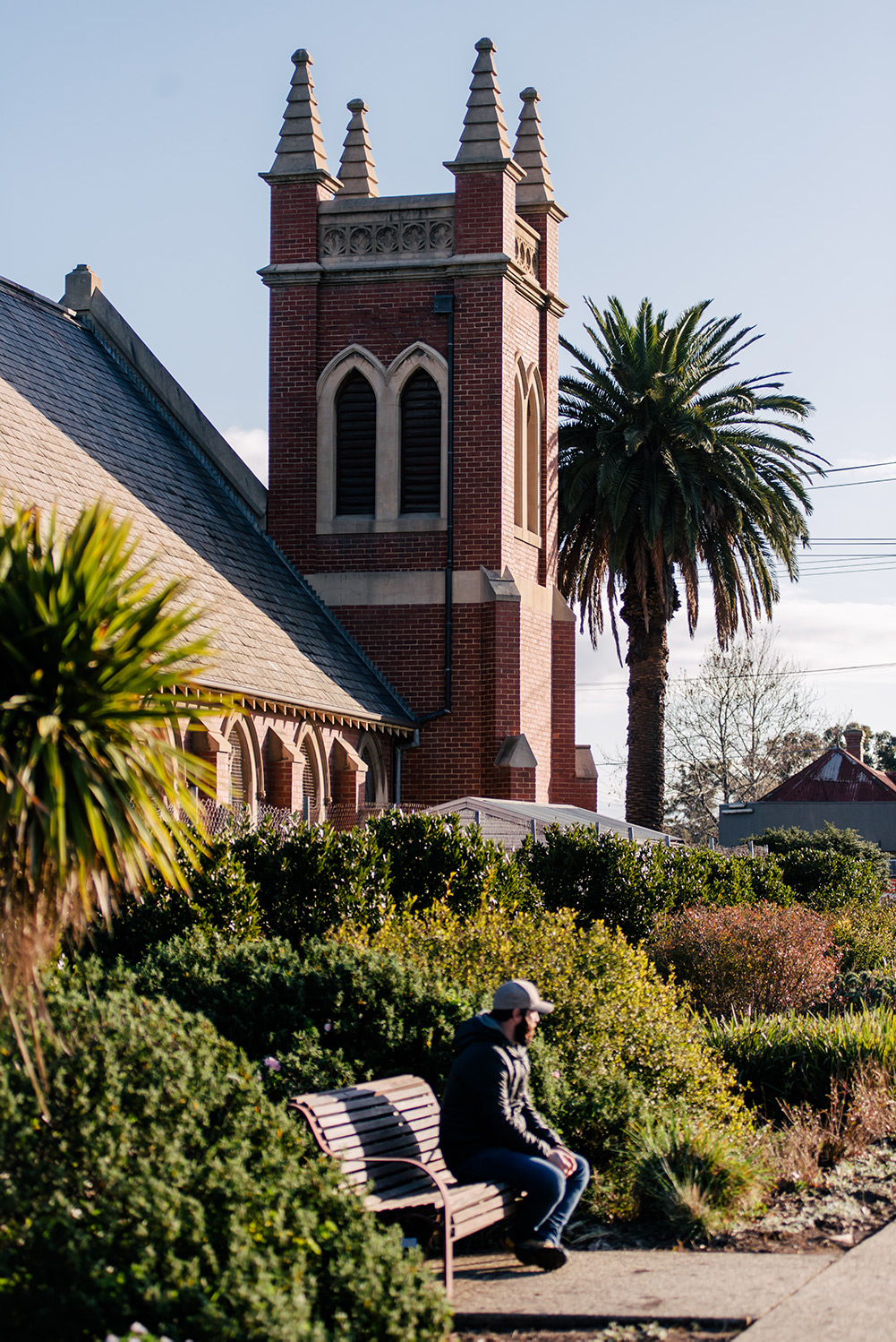 man sitting on bench in front of church