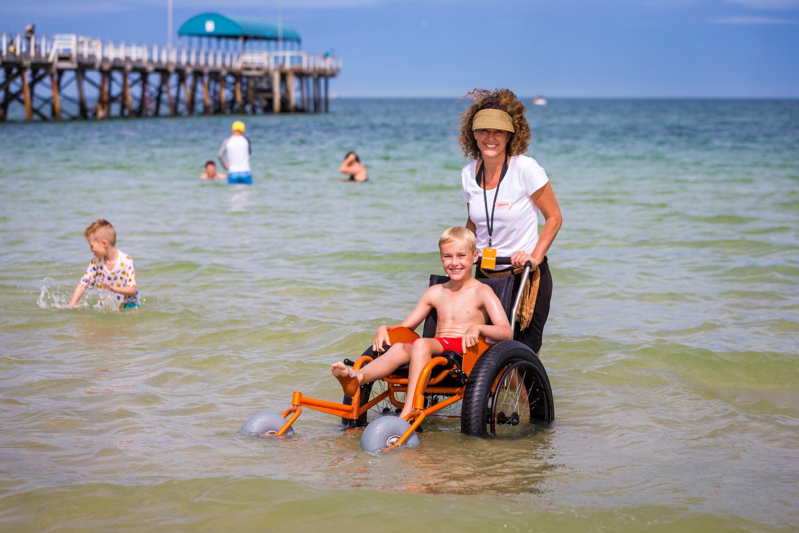 Boy enjoying a swim at Henley Beach in a beach wheelchair