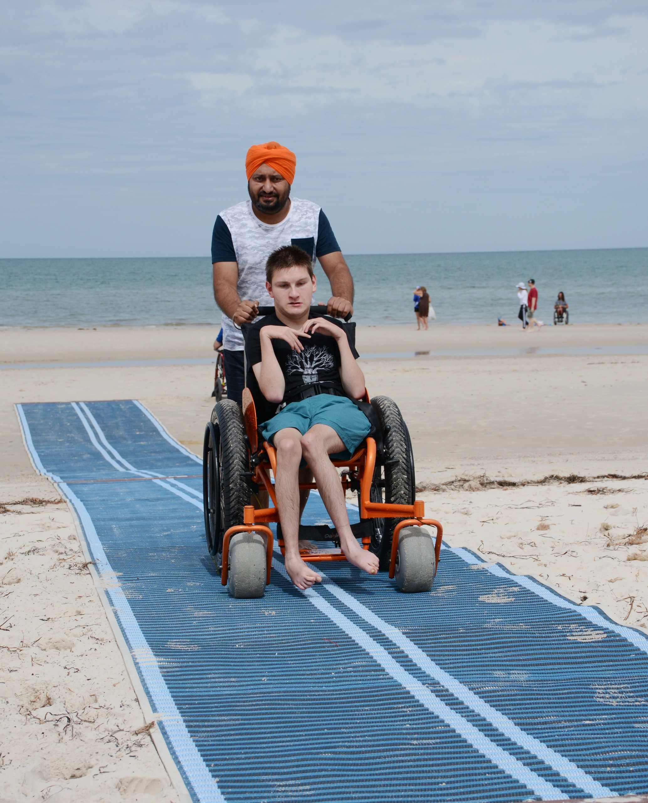Person in wheelchair using accessible beach mats at Henley Beach