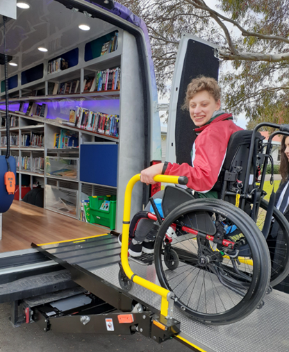 Lady using wheelchair accessible ramp to enter Council's mobile library