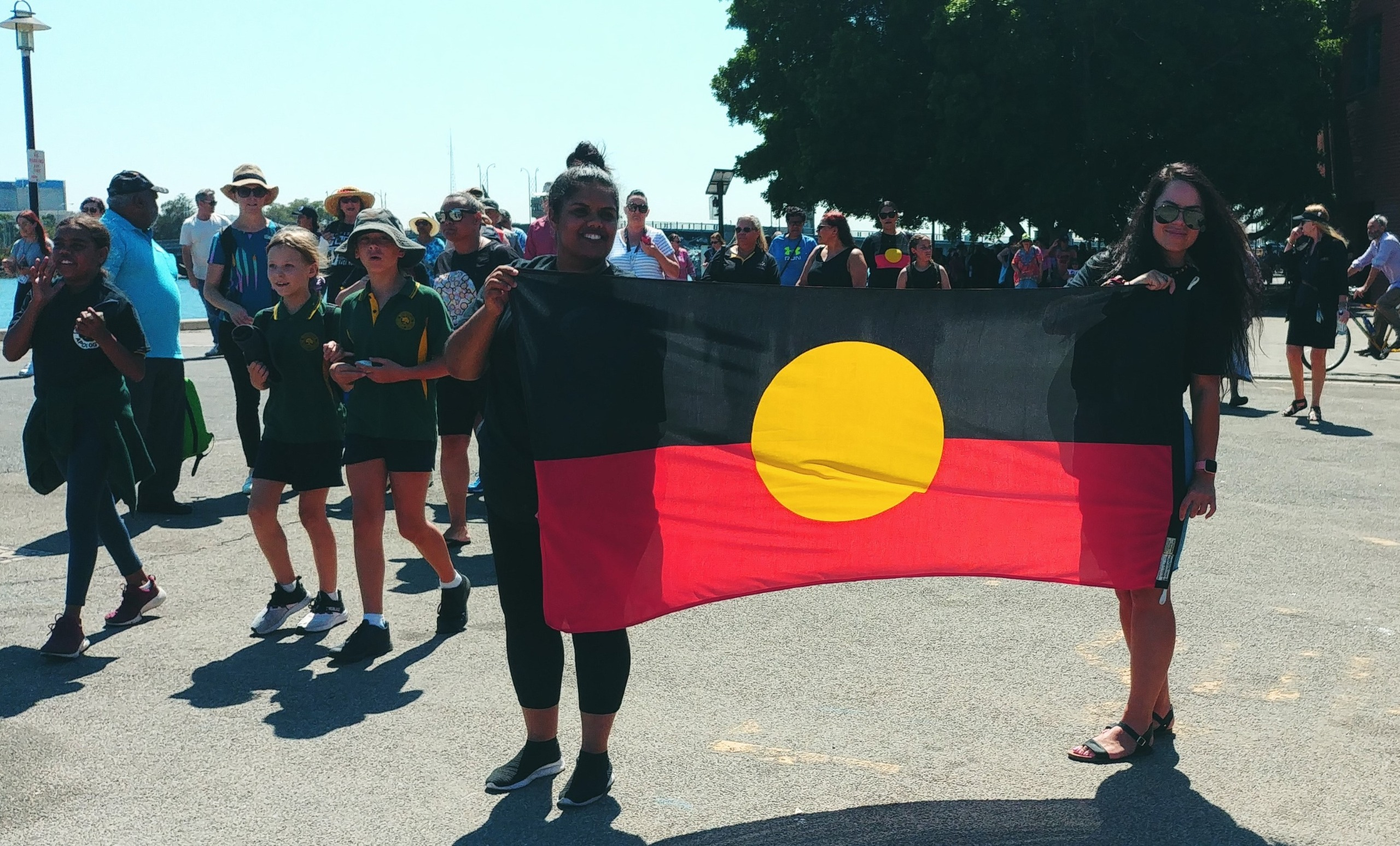 People holding Aboriginal Flag and walking in commemoration event