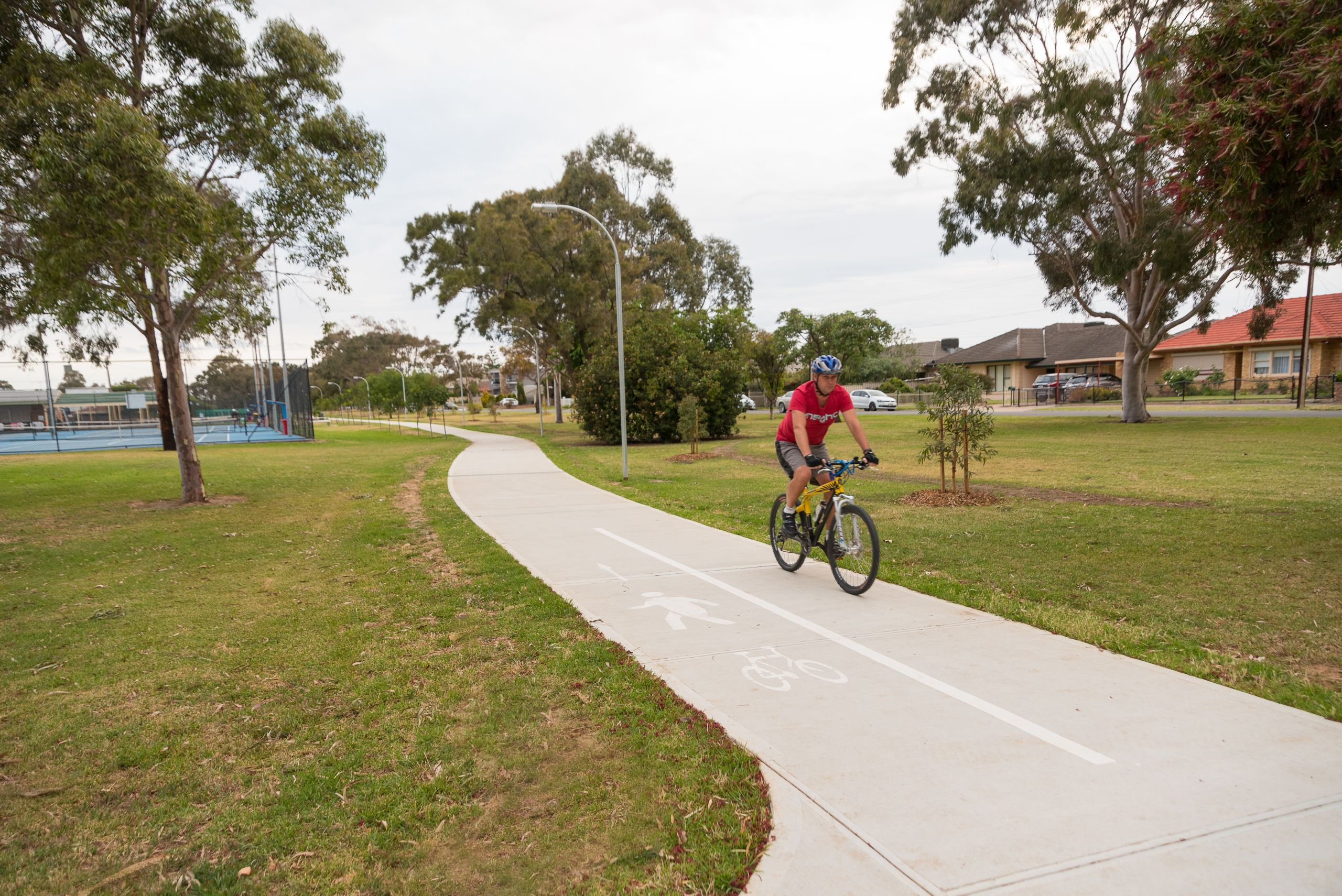 Person cycling along shared user path