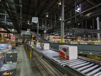 An assembly line in a factory. Boxes moving along a conveyor belt.