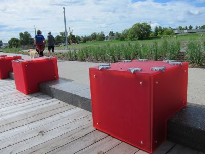 Riverside benches separated by bright red cubes to add colour and style