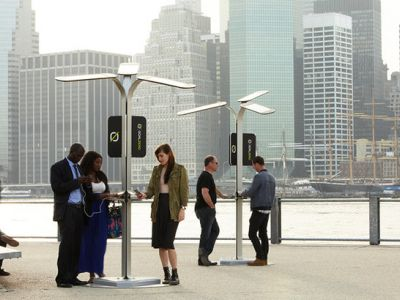 People accessing charging stations built into lamp posts