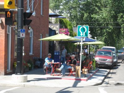 A patio with folding chairs, tables & umbrellas. The sidewalk is between the cafe and the tables & chairs.