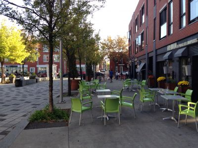 A patio outside of a cafe with moveable tables and chairs. A line of trees between the patio and the street.