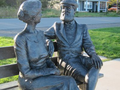 Statues or a woman & a man talking - built into a bench