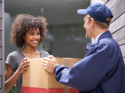 A delivery person handing a box to a young woman.