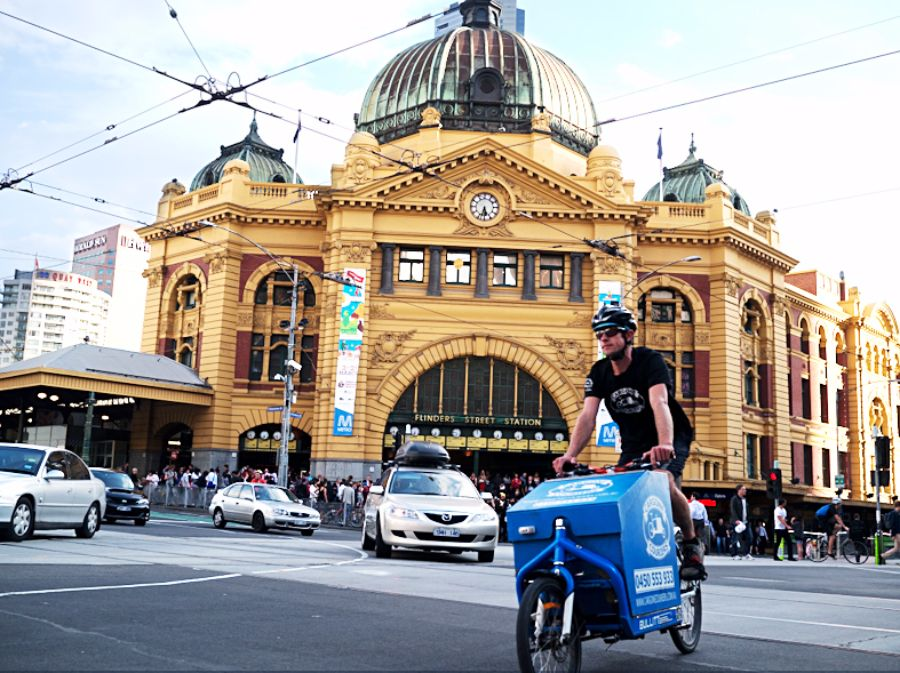 Photo of Flinders Street Station and a man on a bike with a delivery box at the front.
