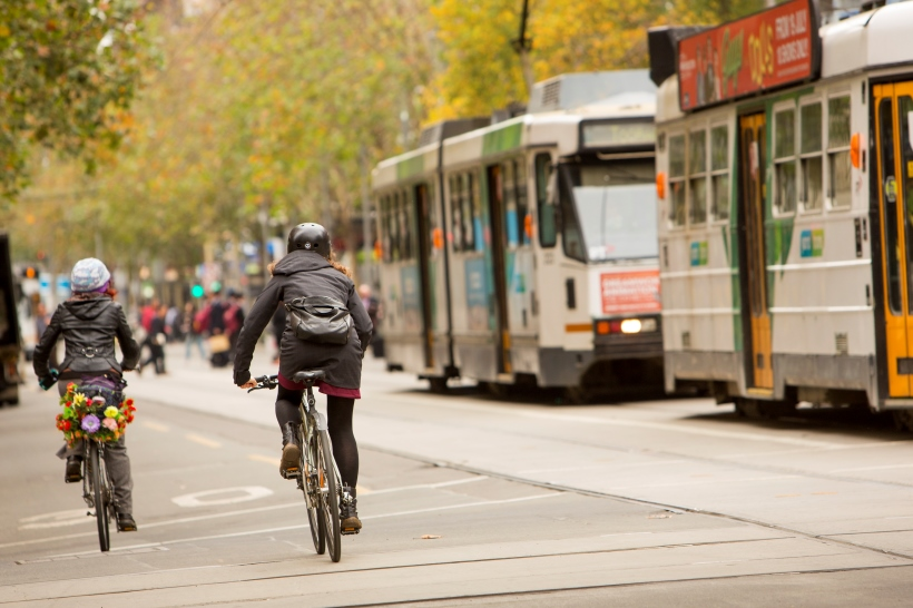Cyclist riding through the city next to a tram