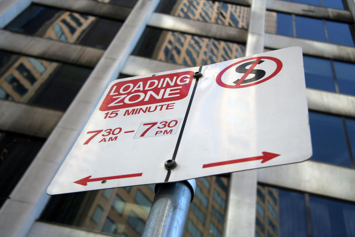 Photo of a loading zone and no standing zone sign, looking from the ground up.