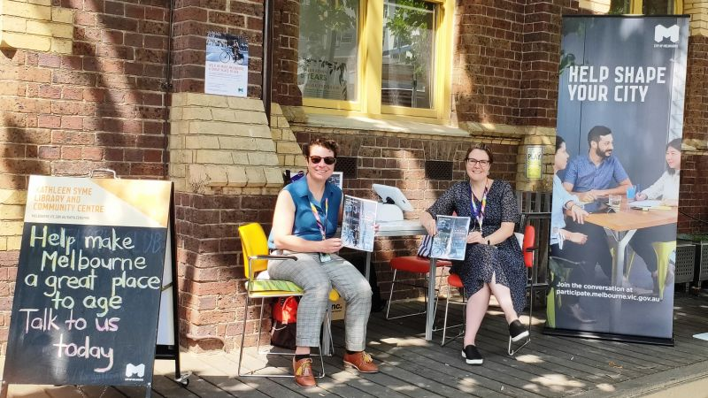 Two female City of Melbourne staff smile while holding copies of the strategy at a table outside the library