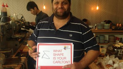 Man holding poster reading 'What shape is your Carlton?' with a shape he drew next to it.