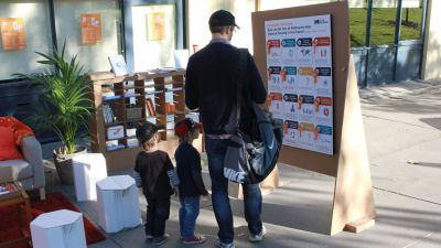 A father and two small children standing in front of the feedback boards.