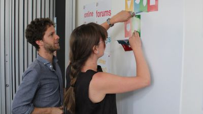 Woman pinning coloured cards to a poster with a man watching.