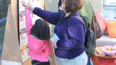 A small girl reaches to move a key on the board while an adult female helps.