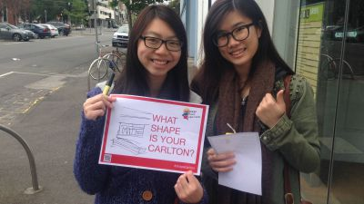 Two girls with glasses holding a sign reading 'What shape is your Carlton?'