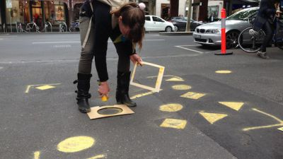 Girl spray painting a yellow circle onto the ground using a stencil