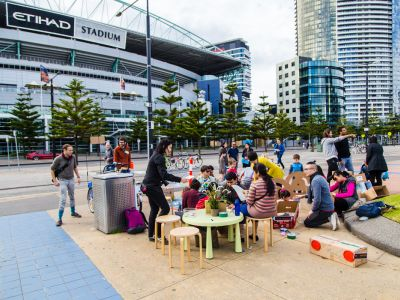 Groups of adults and children sitting around wooden chairs and tables in front of Etihad Stadium.