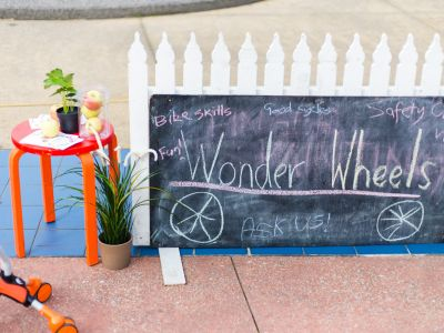 "A small stool with a plant on top next to a blackboard leaning against a white picket fence that reads ""Wonder Wheels""."