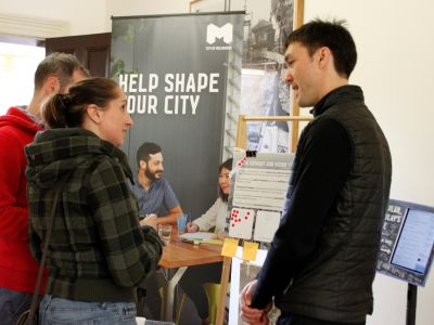 A couple stand facing City of Melbourne staff to provide feedback.