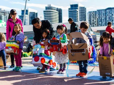 Children line up for the start of a race holding cardboard handmade cars around themselves.