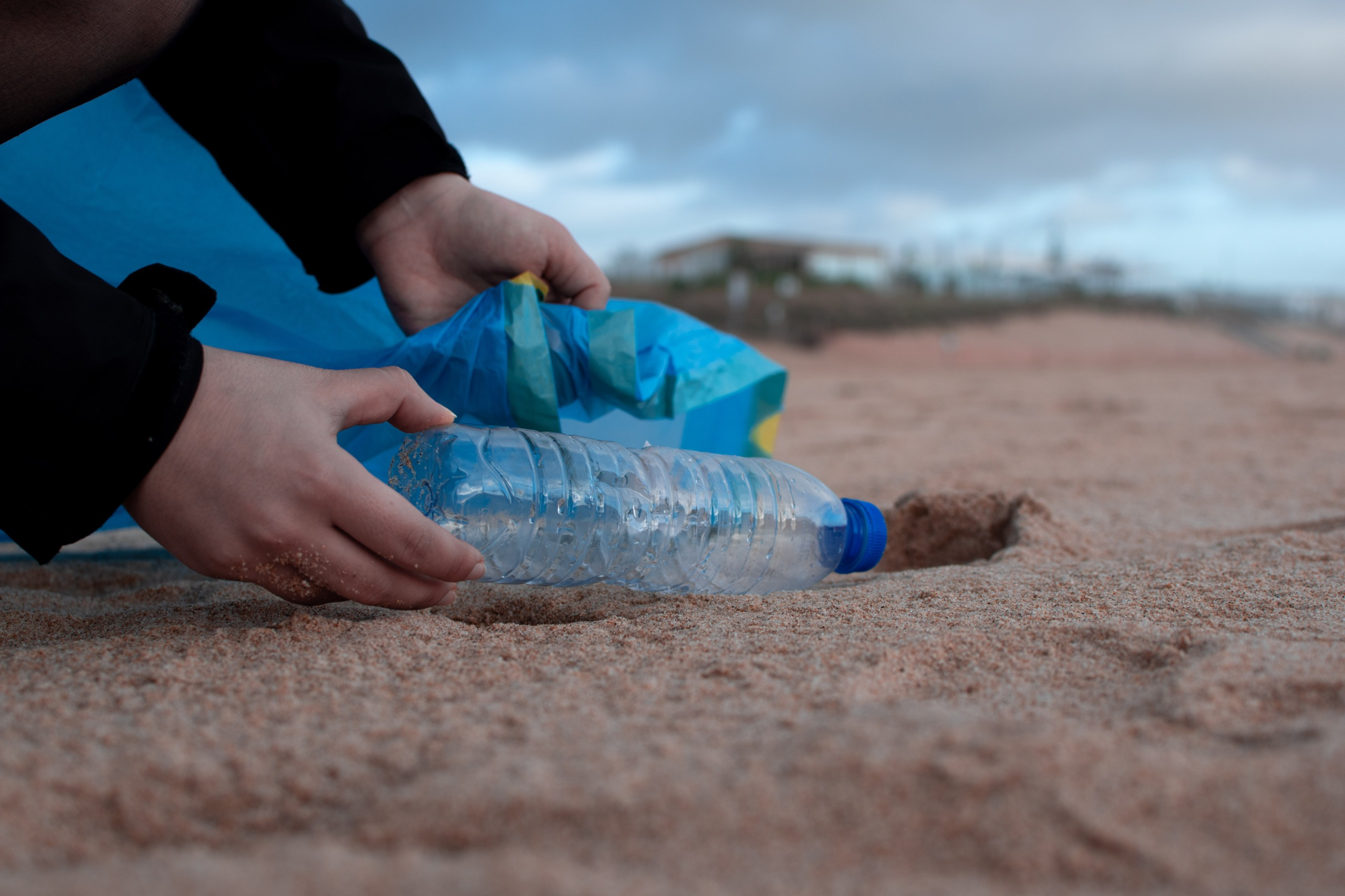 Person collecting bottle from beach
