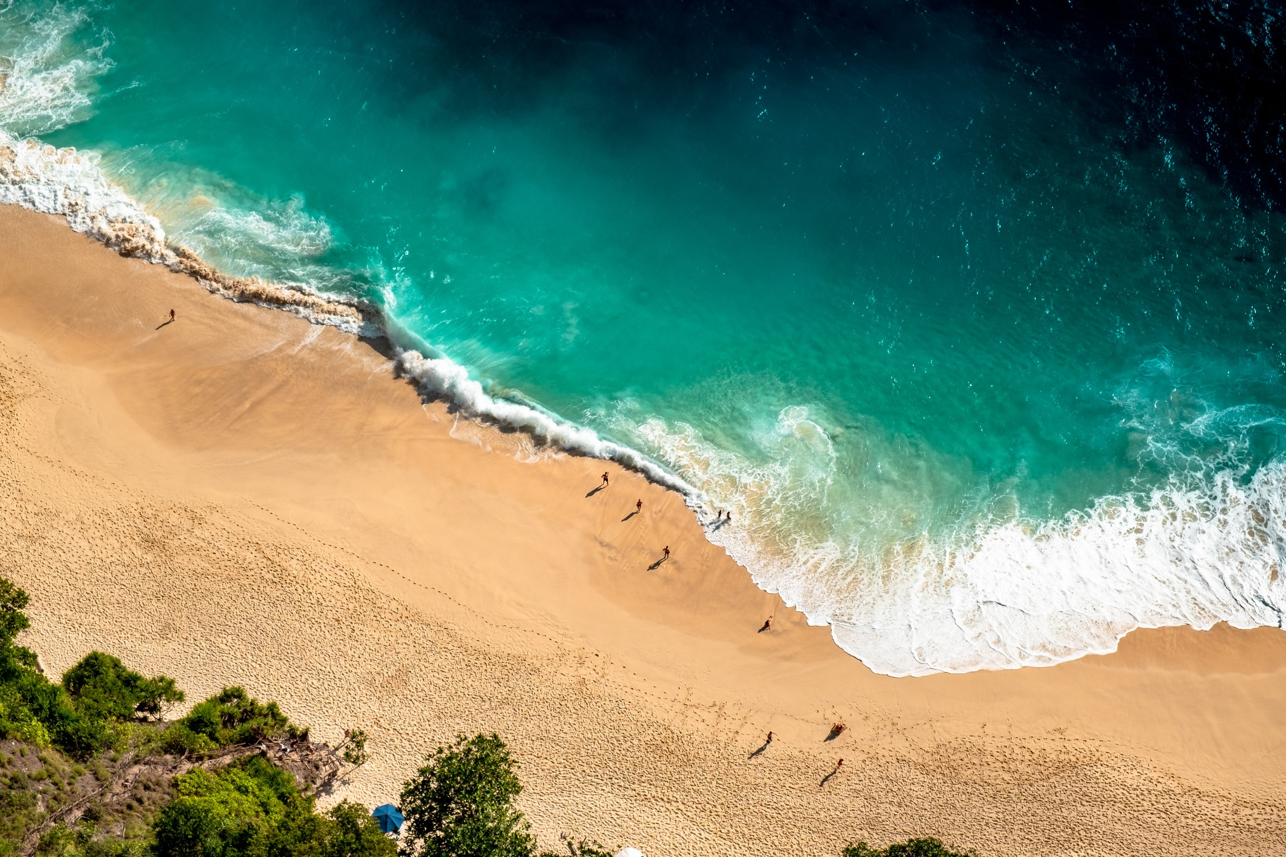 Drone shot of beach with people on it.