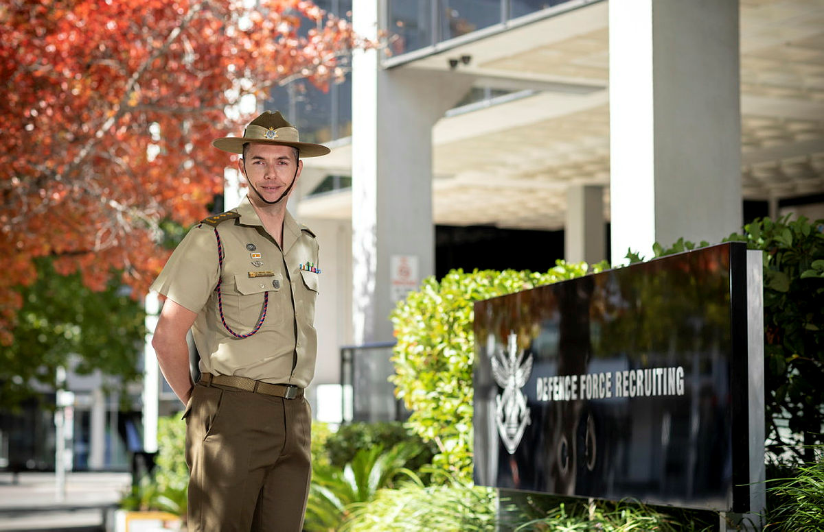 Army soldier standing in front of defence building
