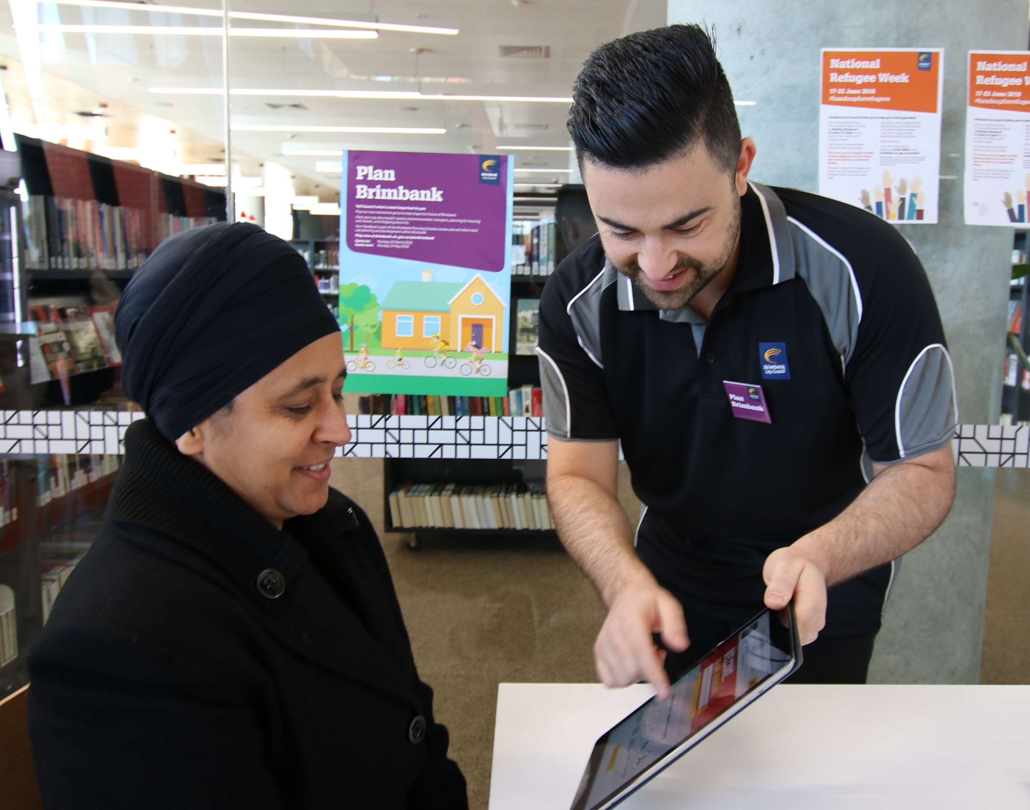 Brimbank council officer assisting a seated lady to play the game on a tablet