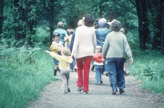 A colour photo of a group of people with children walking down a path