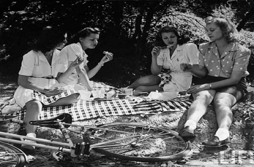 Black and white image of women having a picnic on a sunny day in 1966