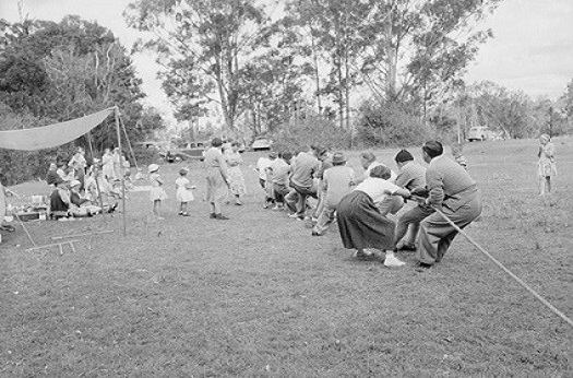 Black and white image of people playing tug of war in 1952