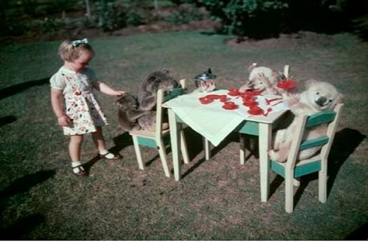 Colour image from 1962 of a children at a toy table with teddy bears