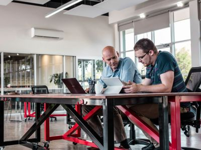 Two people working at a bench style desk
