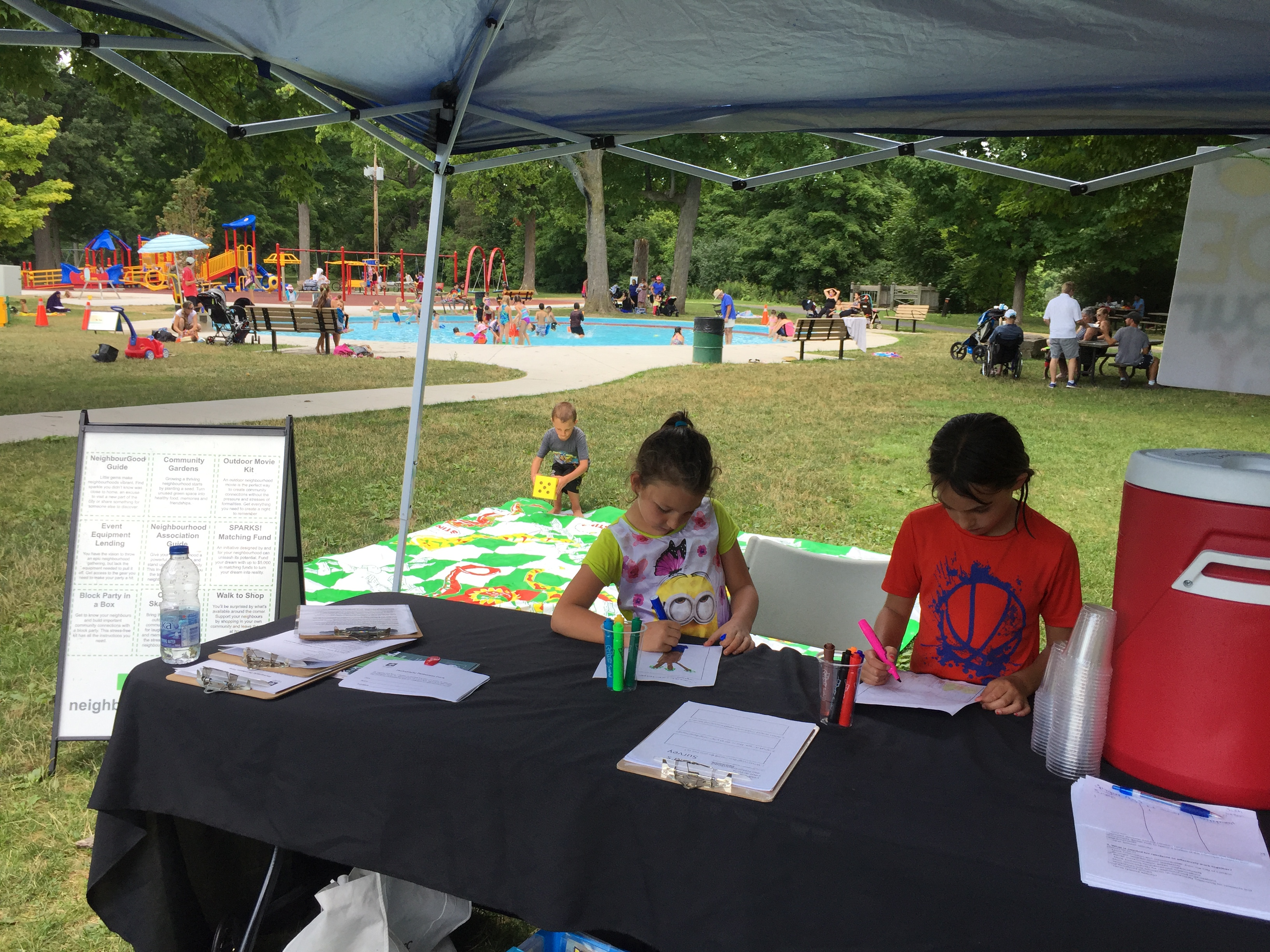 Kids at Springbank Park filling out the Kids Survey and playing Snakes and Ladders.