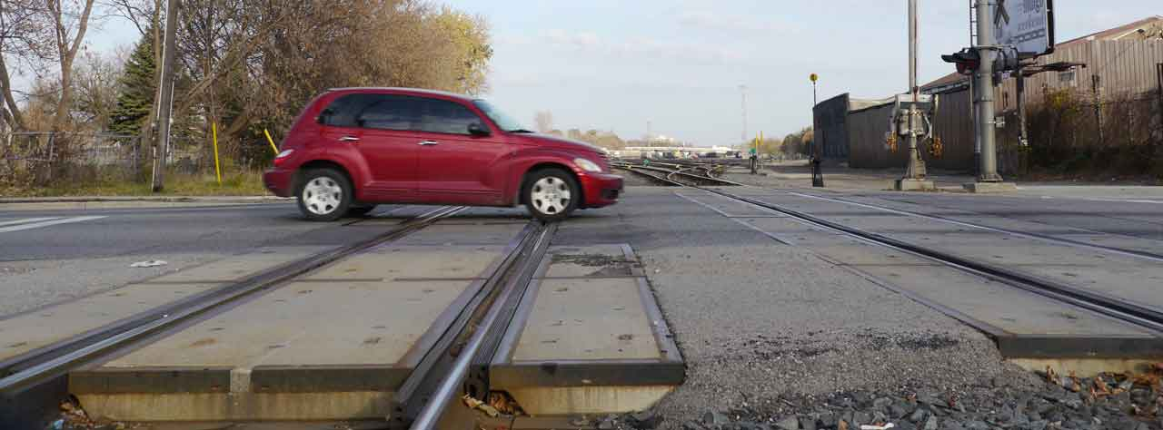red PT cruiser crossing railroad tracks