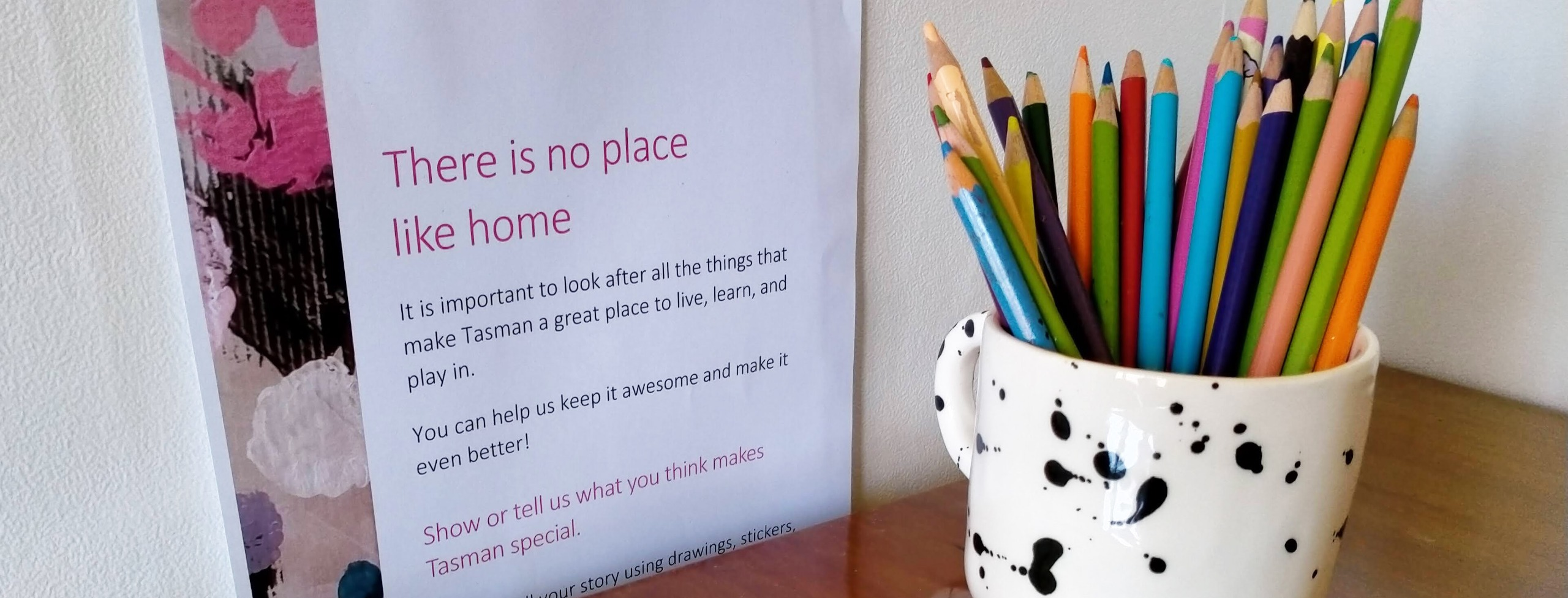 No place like home school competition poster hanging on the wall by a table with a pencil holder