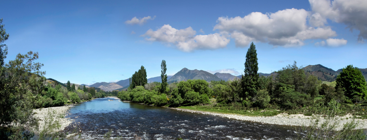 River flowing in a valley with distant mountains in the background